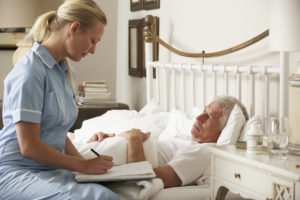 Nurse Visiting Senior Male Patient In Bed At Home Writing Notes.